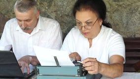 Mujer madura del cuaderno del trabajo del hombre en la máquina de escribir metrajes
