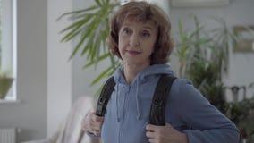Mujer madura del retrato en la sudadera con capucha azul que fija la mochila cómoda negra en su parte posterior Mujer madura en s almacen de video