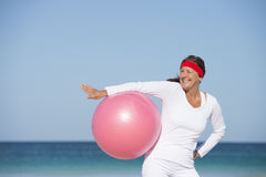 Mujer madura deportiva apta que ejercita la playa Foto de archivo libre de regalías