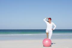 Mujer madura deportiva feliz que ejercita la playa Imagen de archivo libre de regalías