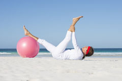 Mujer madura deportiva que ejercita la playa Imagen de archivo