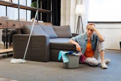 Mujer madura despedida que es cansada extremadamente y que descansa sobre piso fotos de archivo libres de regalías