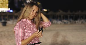 Mujer madura despedir el pelo en la playa de la noche del fondo almacen de metraje de vídeo