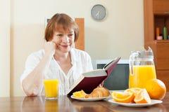 Mujer madura durante el desayuno Imágenes de archivo libres de regalías