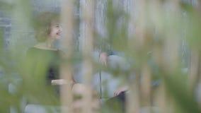 Mujer madura elegante bonita que habla con el hombre joven en la camisa azul que se incorpora en el cierre del sofá La planta sal almacen de video