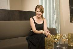 Mujer madura elegante hermosa que se sienta en un sofá Imágenes de archivo libres de regalías
