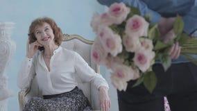 Mujer madura elegante linda hermosa del retrato en la blusa blanca que se sienta en la sonrisa de la butaca El hombre irreconocib almacen de video
