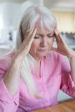 Mujer madura en casa que sufre de dolor de cabeza fotografía de archivo