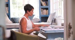 Mujer madura en el escritorio que trabaja en Ministerio del Interior con el ordenador portátil almacen de video