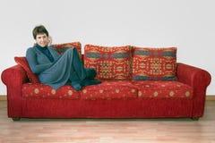 Mujer madura en el sofá, canapé con el teléfono móvil Charla, chisme Imagen de archivo