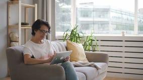 Mujer madura en la camiseta blanca que se sienta en el sofá cómodo y el mensaje que mecanografía almacen de video