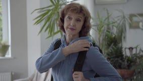 Mujer madura en la sudadera con capucha azul que fija la mochila cómoda negra en su parte posterior metrajes