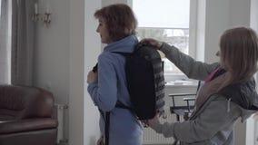 Mujer madura en la sudadera con capucha azul que fija la mochila c?moda negra en su parte posterior almacen de metraje de vídeo