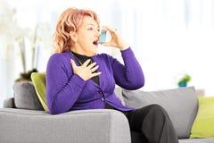 Mujer madura en un sofá que toma el tratamiento del asma con el inhalador en h Imagenes de archivo