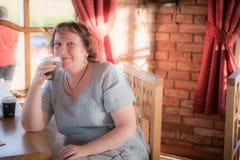 Mujer madura en una sonrisa del café Imagen de archivo