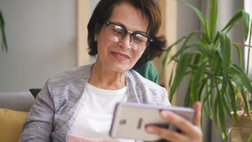 Mujer madura en vidrios, con el pelo marrón teniendo vídeo almacen de metraje de vídeo