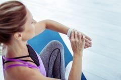 Mujer madura enfocada que verifica pulso en gimnasio fotografía de archivo libre de regalías