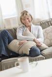 Mujer madura feliz con el amortiguador que se sienta en el sofá Imágenes de archivo libres de regalías