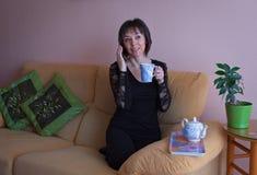 Mujer madura feliz en camisa negra imagenes de archivo