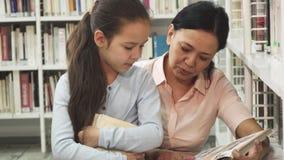 Mujer madura feliz magnífica que lee un libro a su pequeña hija almacen de metraje de vídeo