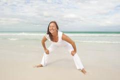 Mujer madura feliz que ejercita la playa del océano Fotografía de archivo