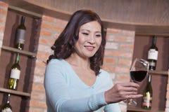 Mujer madura feliz que examina el vino rojo en una degustación de vinos Imagen de archivo libre de regalías