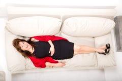 Mujer madura hermosa que se relaja en el sofá en casa imagen de archivo