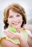 Mujer madura hermosa que sostiene una manzana Foto de archivo