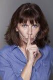 Mujer madura hermosa severa que quiere mantener cosas confidenciales Imagen de archivo