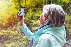Mujer madura mayor atractiva agradable con el pelo gris brillante que toma las fotos y los selfies al aire libre imagen de archivo libre de regalías