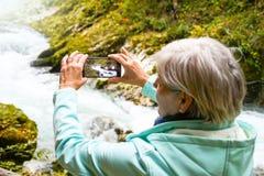 Mujer madura mayor atractiva agradable con el pelo gris brillante que toma las fotos y los selfies al aire libre imagenes de archivo