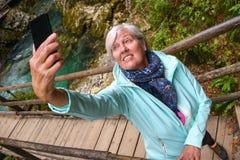 Mujer madura mayor atractiva agradable con el pelo gris brillante que toma las fotos y los selfies al aire libre fotos de archivo libres de regalías