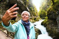 Mujer madura mayor atractiva agradable con el pelo gris brillante que toma las fotos y los selfies al aire libre foto de archivo