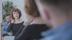 Mujer madura mayor bonita que considera en el espejo su reflexión, tocando su pelo que se sienta delante del hombre joven almacen de video