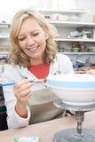 Mujer madura que adorna el cuenco en clase de la cerámica Fotografía de archivo
