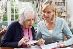 Mujer madura que ayuda al vecino mayor con las finanzas caseras fotos de archivo libres de regalías