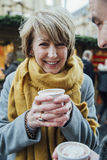 Mujer madura que bebe el chocolate caliente en el mercado de la Navidad Imágenes de archivo libres de regalías