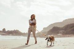 Mujer madura que camina su perro en la playa foto de archivo