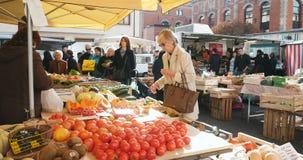 Mujer madura que compra tomates orgánicos en el mercado de la comida almacen de metraje de vídeo