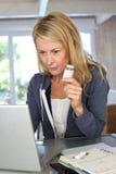 Mujer madura que comprueba la composición de la medicación en Internet Fotos de archivo