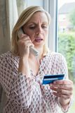 Mujer madura que da los detalles de la tarjeta de crédito en el teléfono foto de archivo libre de regalías