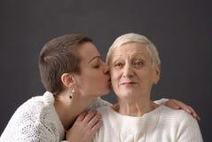 Mujer madura que da un beso en la mujer mayor Imagen de archivo