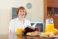 Mujer madura que desayuna con el libro Imagenes de archivo