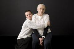 Mujer madura que detiene a la mujer mayor en sus brazos Imagen de archivo