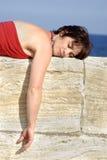Mujer madura que duerme en una pared Foto de archivo