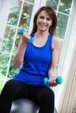 Mujer madura que ejercita con la bola y los pesos suizos en casa foto de archivo