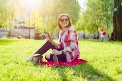 Mujer madura que escucha la música en los auriculares Se sienta en la hierba en el parque, descansando disfruta de la naturaleza imagenes de archivo