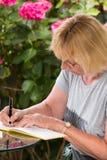 Mujer madura que firma un libro de visitas Imágenes de archivo libres de regalías