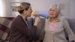 Mujer madura que habla en megáfono a la mujer mayor sorda, problemas de la audición, broma almacen de metraje de vídeo