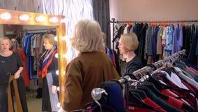 Mujer madura que intenta el espejo delantero de la nueva chaqueta mientras que hace compras en tienda de la moda almacen de video